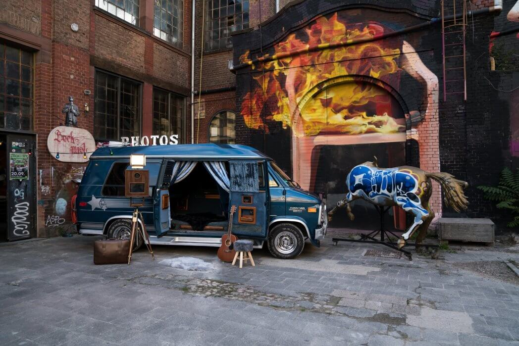 Vintage Chevrolet Fotobus mit einer Retro Holz Fotobox steht vor einer Graffiti Wand.