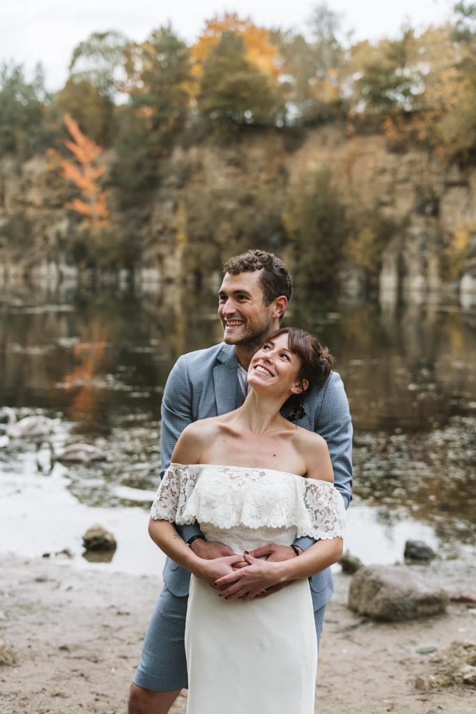 Braut liegt im Arm ihres Bräutigams und strahlt ihn an.