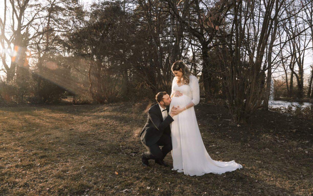 Bräutigam küsst den Babybauch seiner Braut