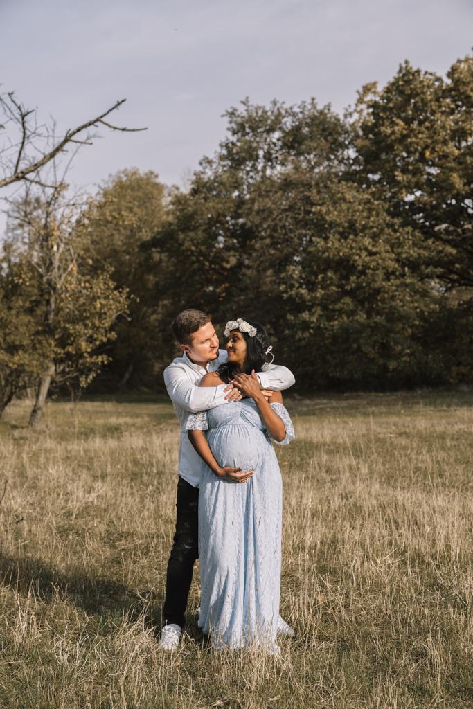Ehepaar steht auf einer Wiese und der Mann umarmt seine schwangere Frau.