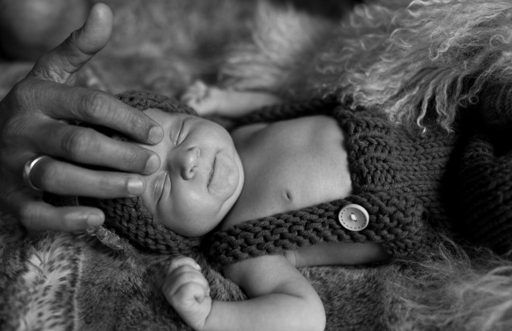 Hand vom Papa streichelt die Stirn des Neugeborenen.