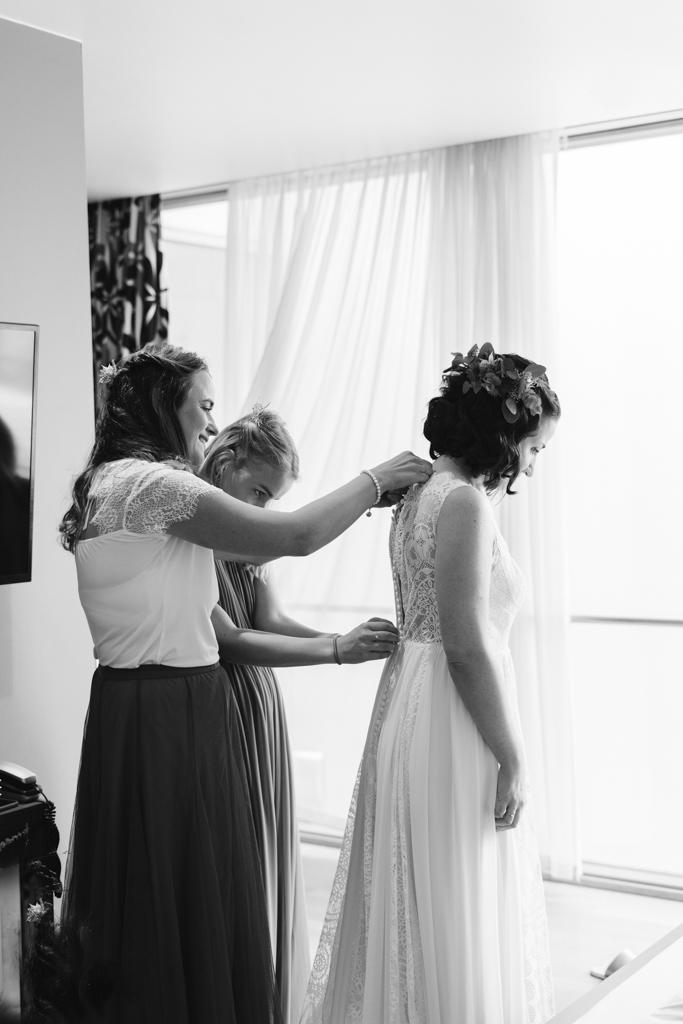 Trauzeuginnen machen das Hochzeitkleid der Braut zu.