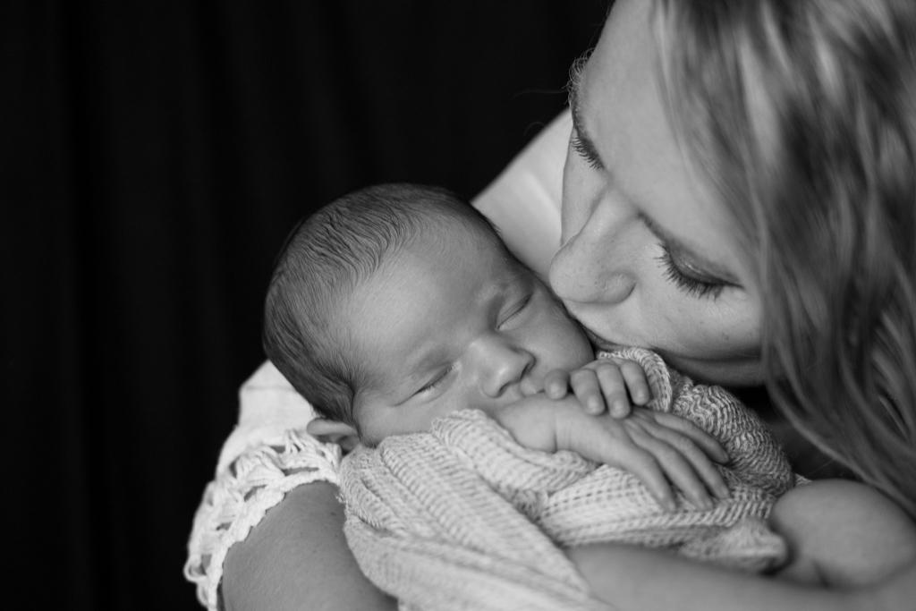 Mama küsst ihr Neugeborenes Baby auf die Backe.