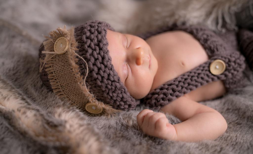 Neugeborenes bei Babyshooting mit Mütze und Fell.