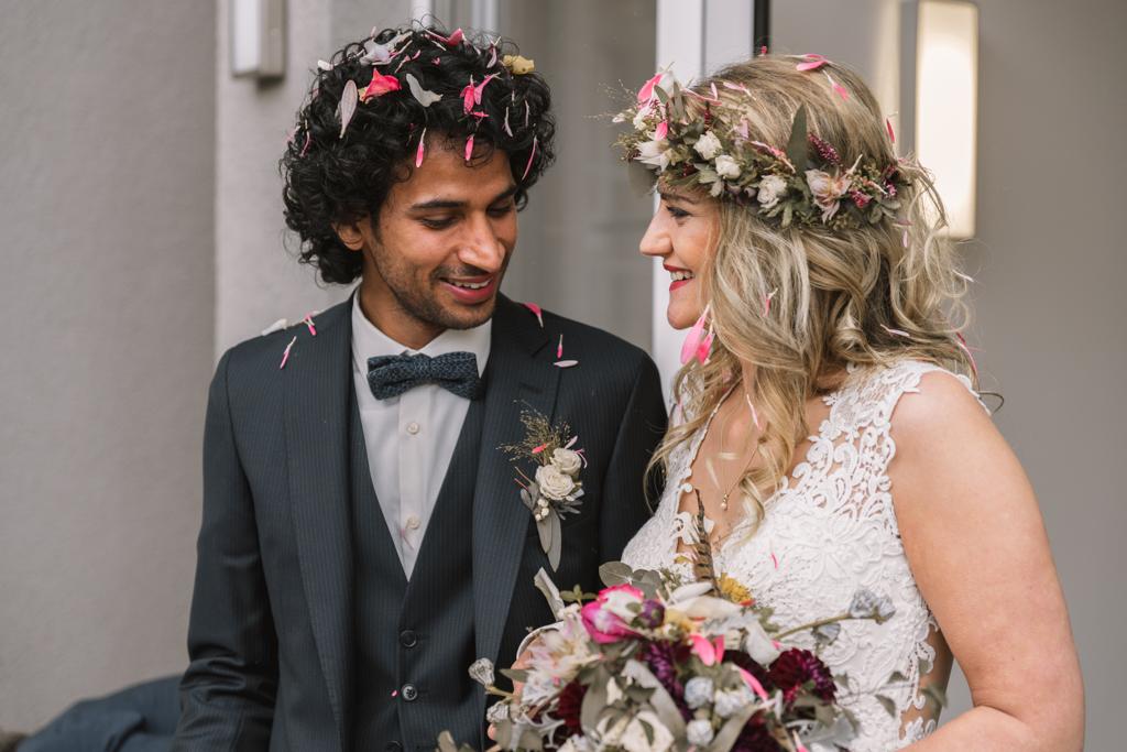 Brautpaar vor dem Standesamt mit Blütenblättern in den Haaren.
