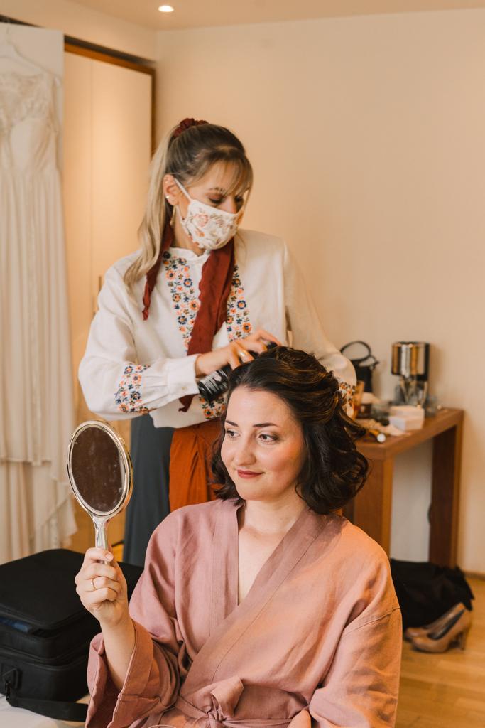Braut schaut in den Handspiegel beim Haarstyling.