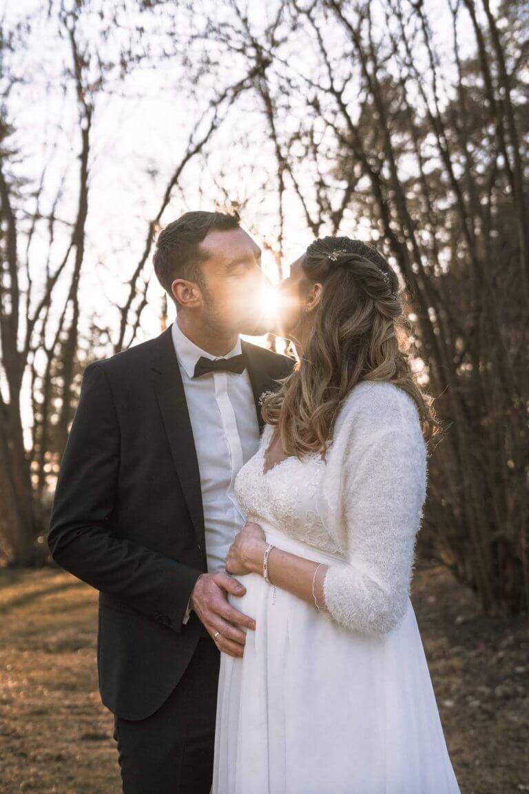 Brautpaar küsst sich mit Sonnenstrahlen im Gesicht