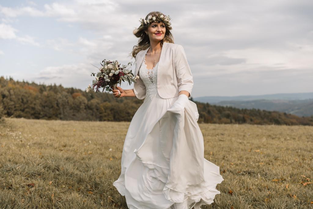 Bohemian Braut steht mit ihrem Brautstrauß auf der Wiese.
