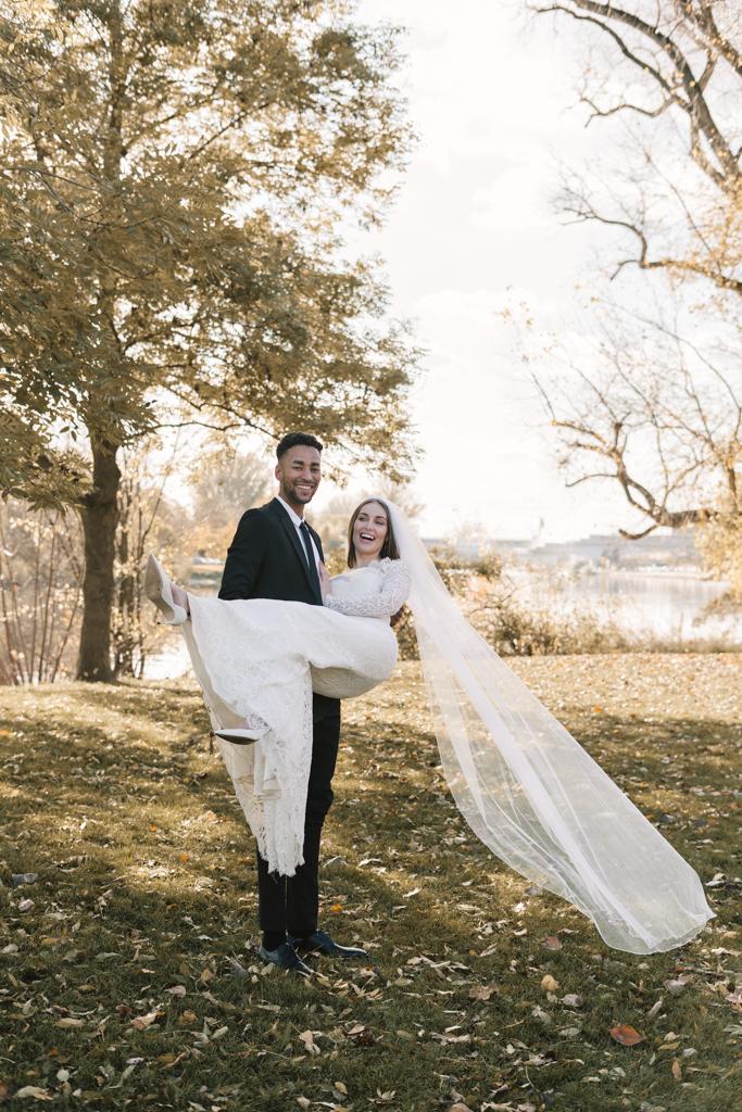 Bräutigam hält die Braut in den Armen hoch.