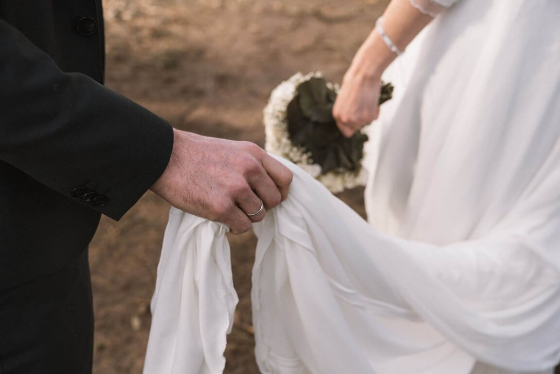 Bräutigam hält in der Ringhand das Brautkleid
