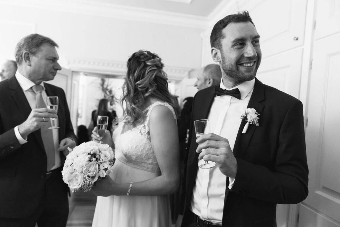 Brautpaar und Hochzeitsgesellschaft beim Sektempfang