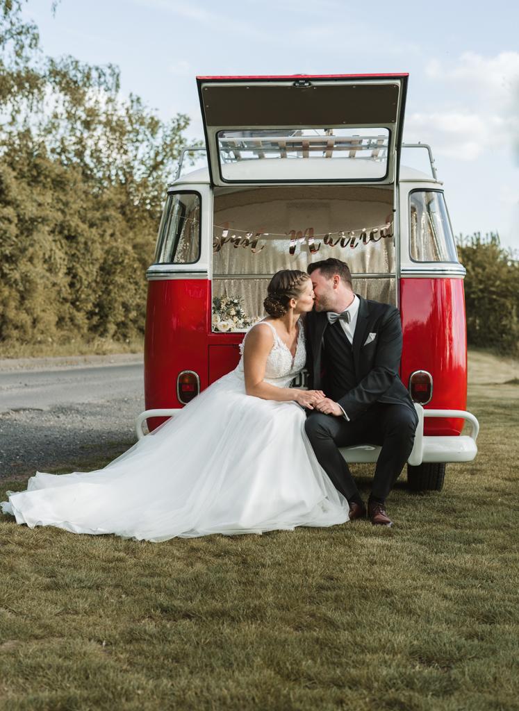 Brautpaar sitzt im Kofferraum vom T1 Bus und küsst sich.