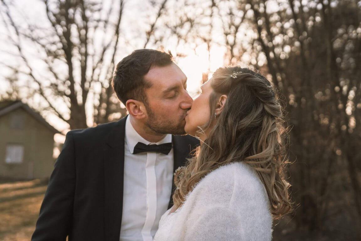 Brautpaar steht draußen und küsst sich bei Sonnenschein