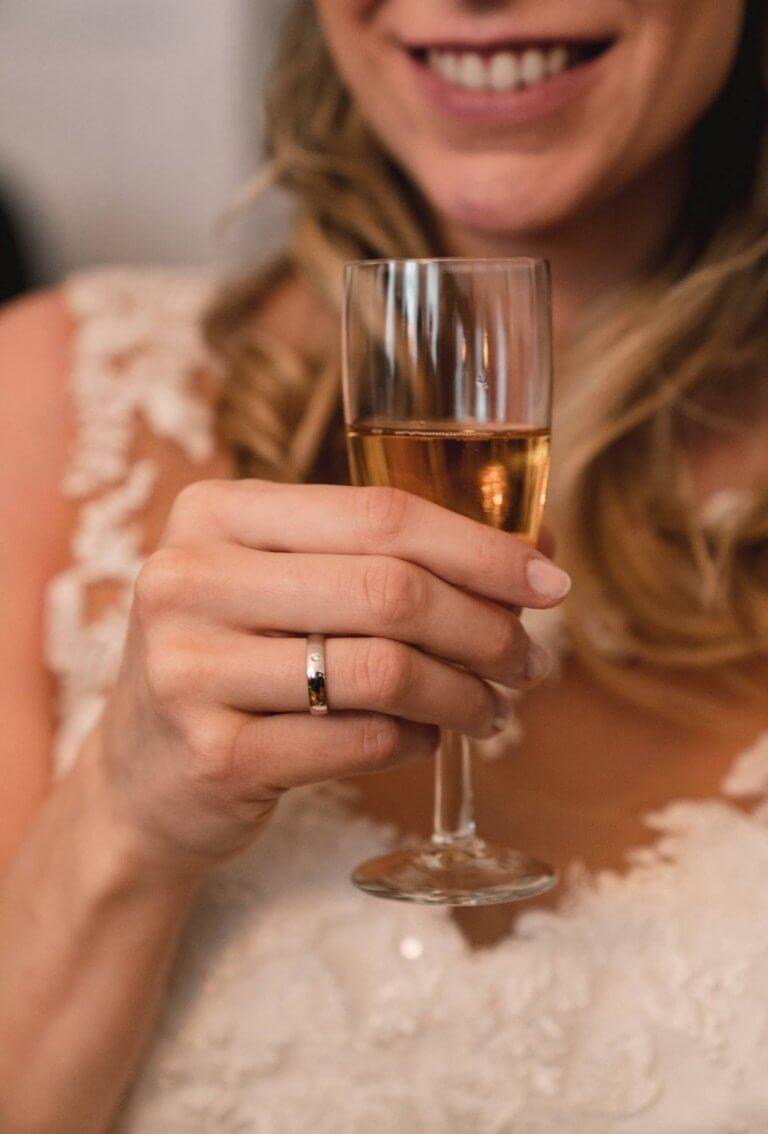 Braut hält Sektglas in der Hand mit Ehering