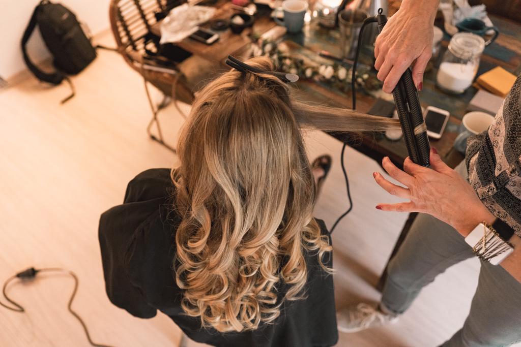 Braut bekommt die Haare gestyled