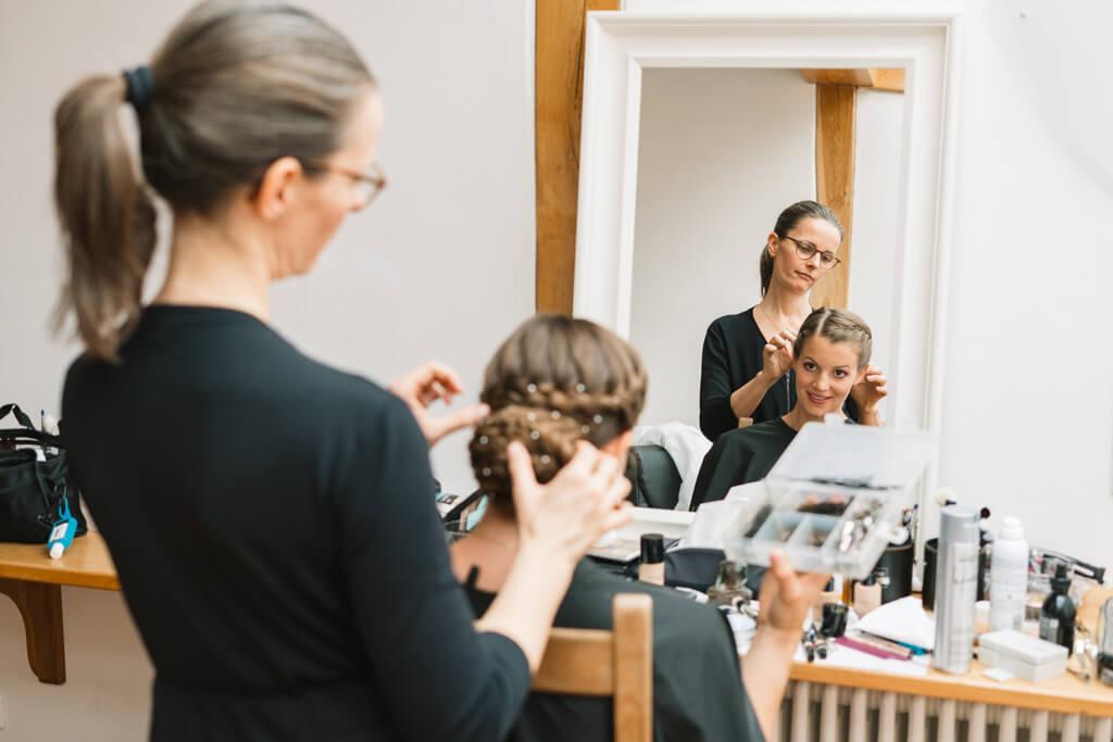 Braut beim Haarstyling schaut in den Spiegel.