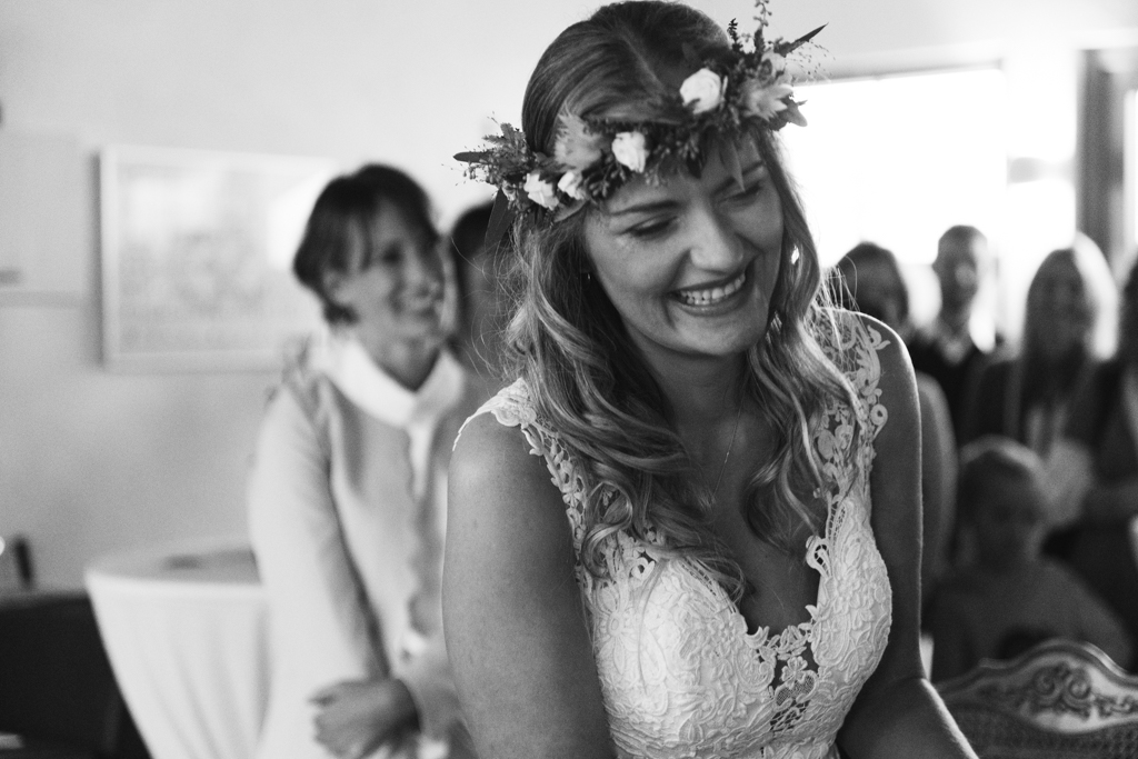 Braut lacht voller Emotionen in die Kamera während der Hochzeit.