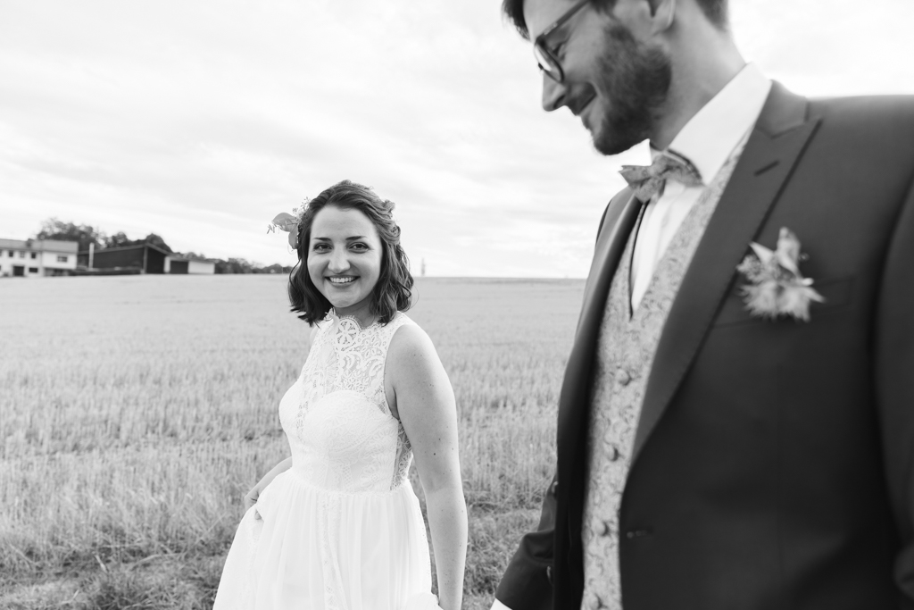 Braut läuft an der Hand des Bräutigams und strahlt in die Kamera.