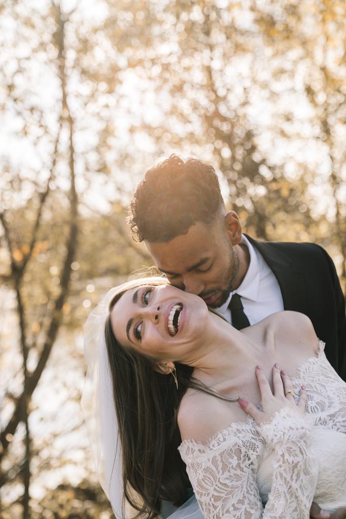 Braut lacht in der Umarmung und dem Kuss ihres Bräutigams.