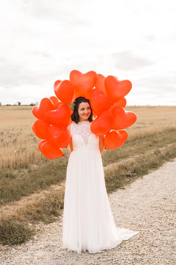 Braut hält rote Herz Luftballons hinter dem Rücken.