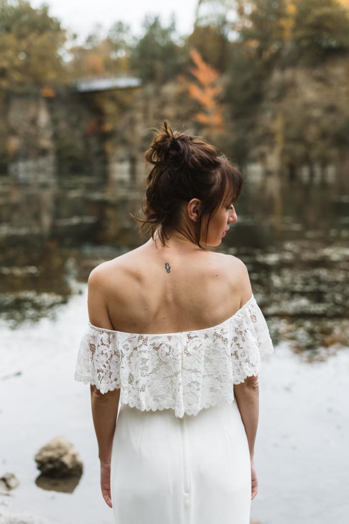 Braut zeht mit dem Rücken an einem See.