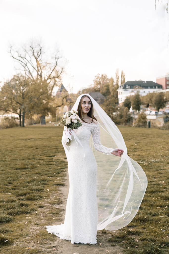 Braut auf einer grünen Wiese mit ihrem Brautstrauß und Schleppe in der Hand.