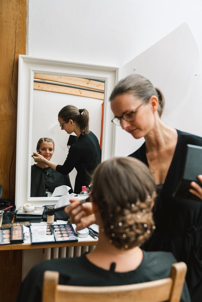 Braut schaut in den Spiegel, während sie geschminkt wird.