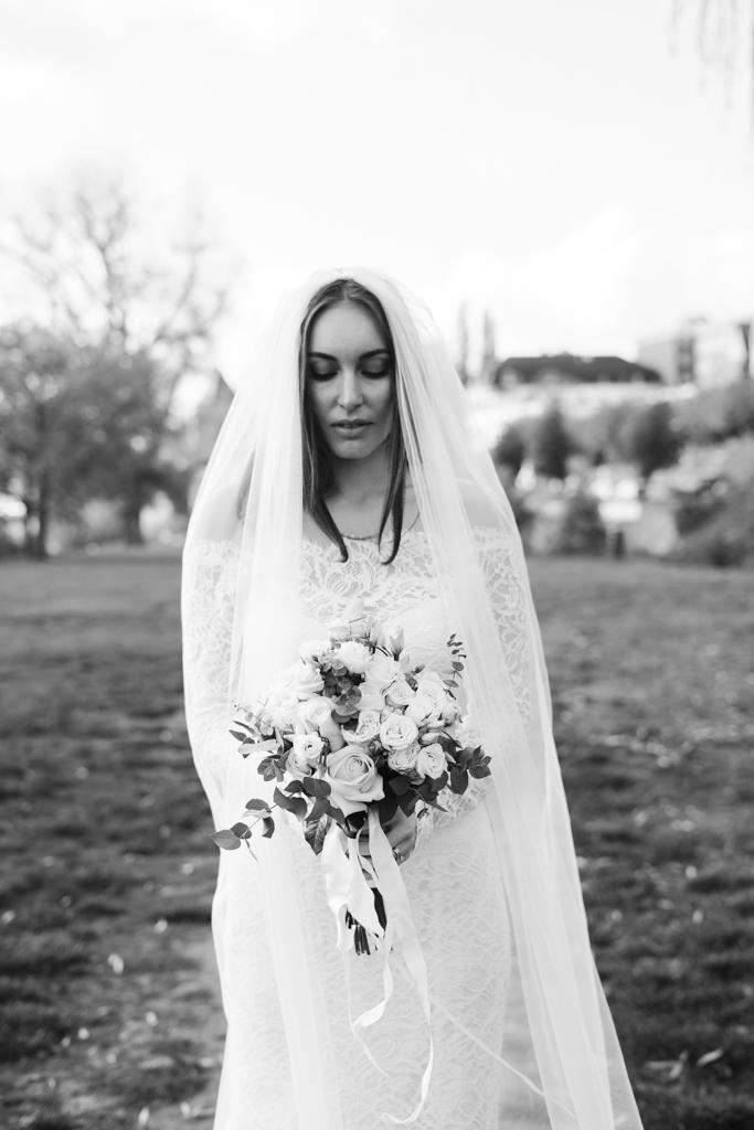 Schwarz weiß Bild einer bildschönen Braut mit ihrem Brautstrauß.