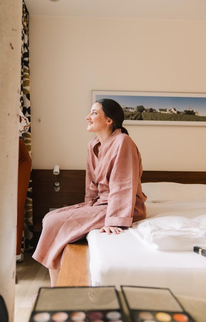 Braut sitzt auf dem Bett im Hotelzimmer.