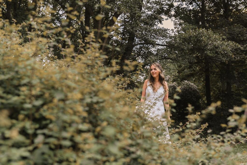 Braut versteckt sich hinter einem Busch damit ihr Bräutigam sie noch nicht sieht.