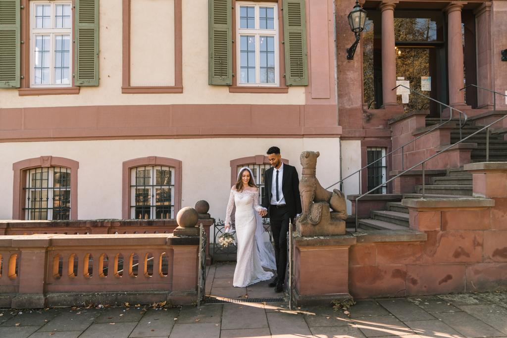 Brautpaar verlässt das Standesamt auf dem Weg in den Schlossgarten.
