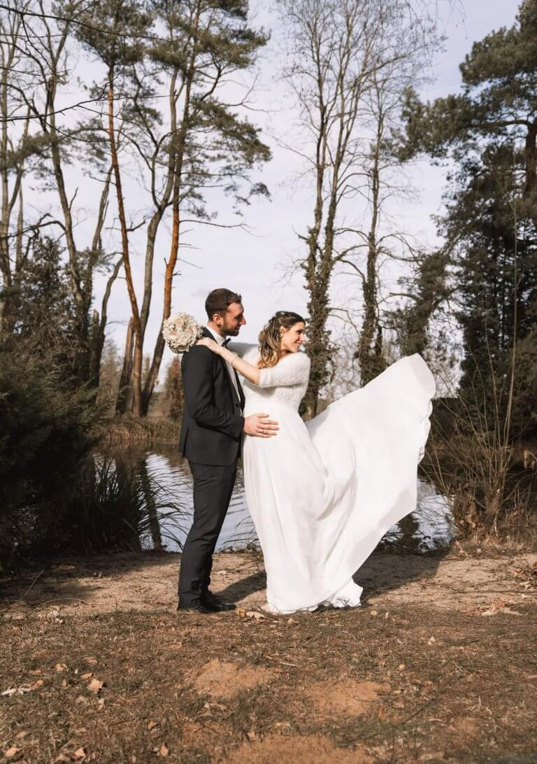Brautpaar steht vor einem See das Brautkleid weht im Wind