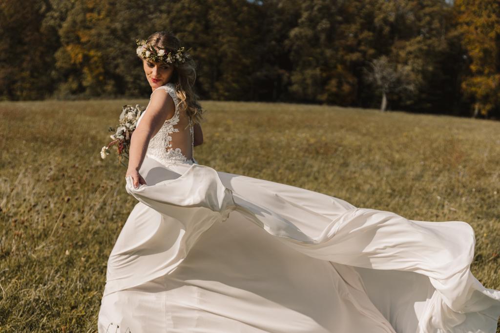 Braut lässt ihr Brautkleid im Wind wehen.