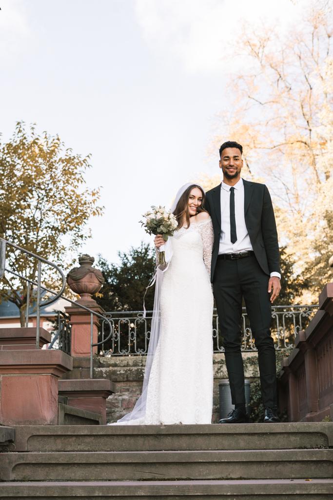 Brautpaar steht auf der Treppe voller Freude nach der standesamtlichen Hochzeit.