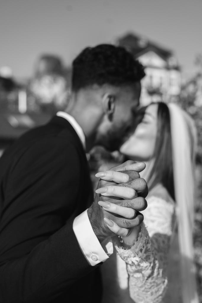 Engumschlungene Hände des Brautpaares während die Beiden sich küssen.