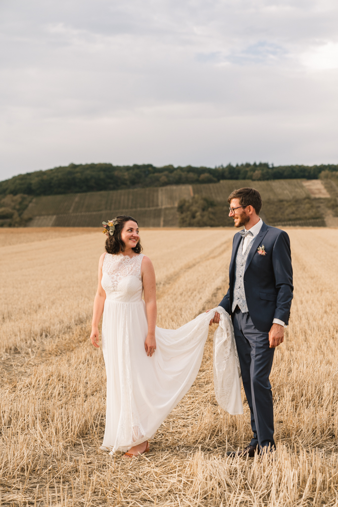 Bräutigam hält die Schleppe des Brautkleides seiner Frau.