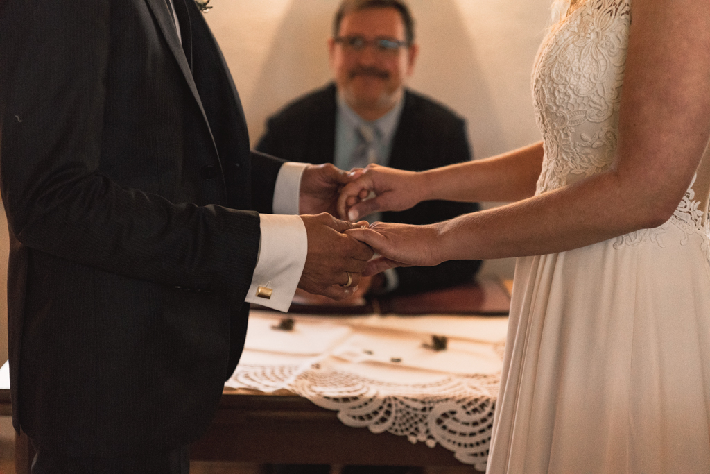 Brautpaar stehen und halten Hände während der Ehegelöbnis im Standesamt.