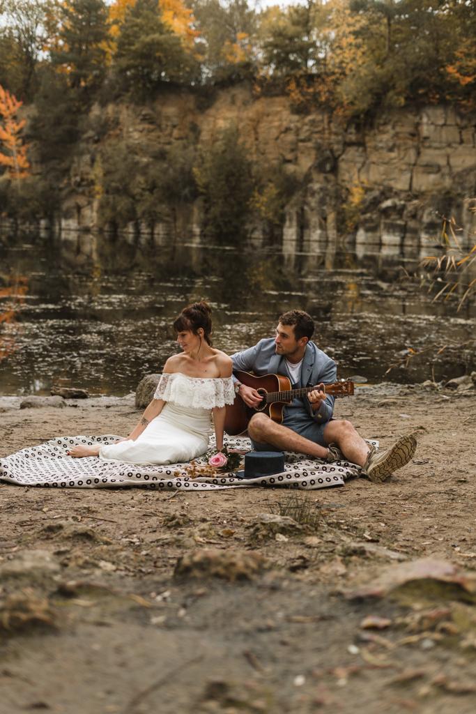 Brautpaar sitzt auf einer picknick Decke und der Bräutigam spielt Gitarre.