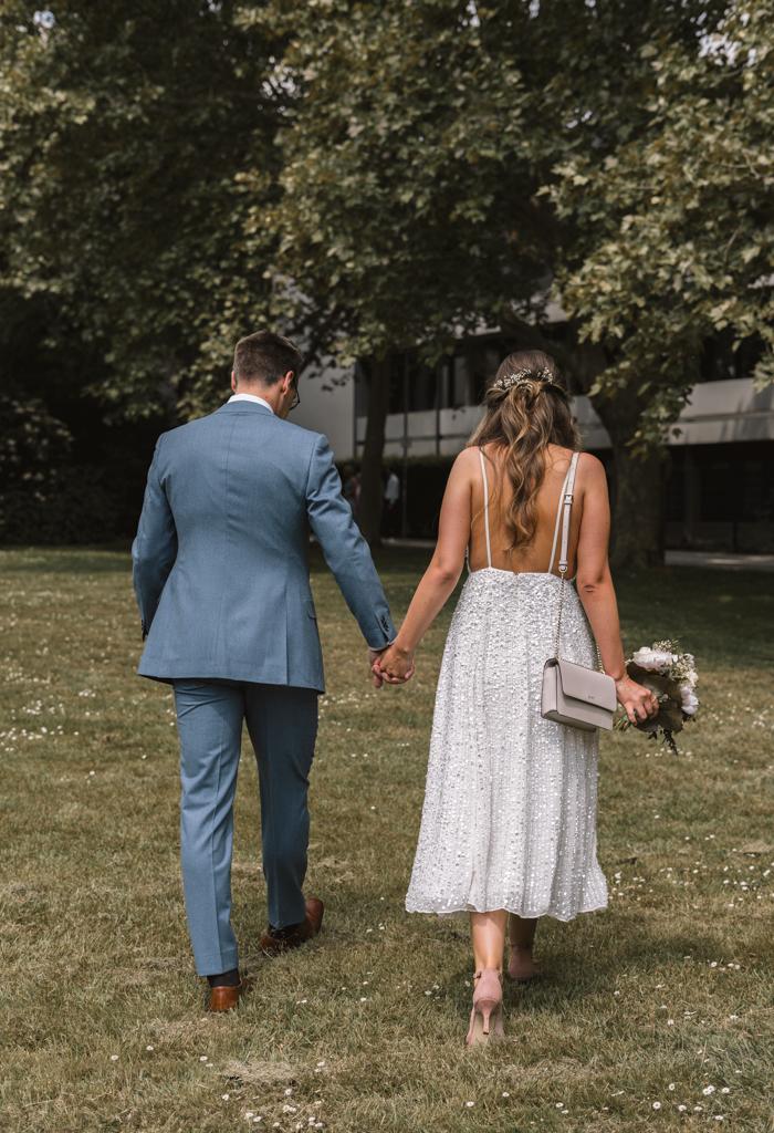 Brautpaar von hinten läuft über eine Wiese zum Standesamt in Königstein.
