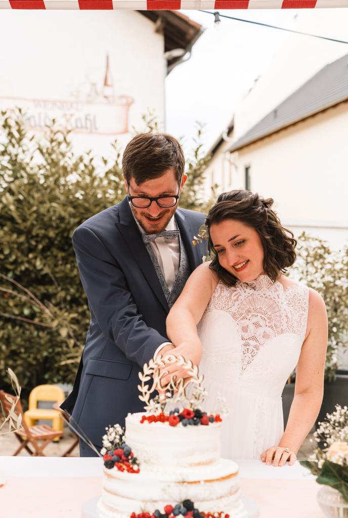 Brautpaar schneidet die Hochzeitstorte an.