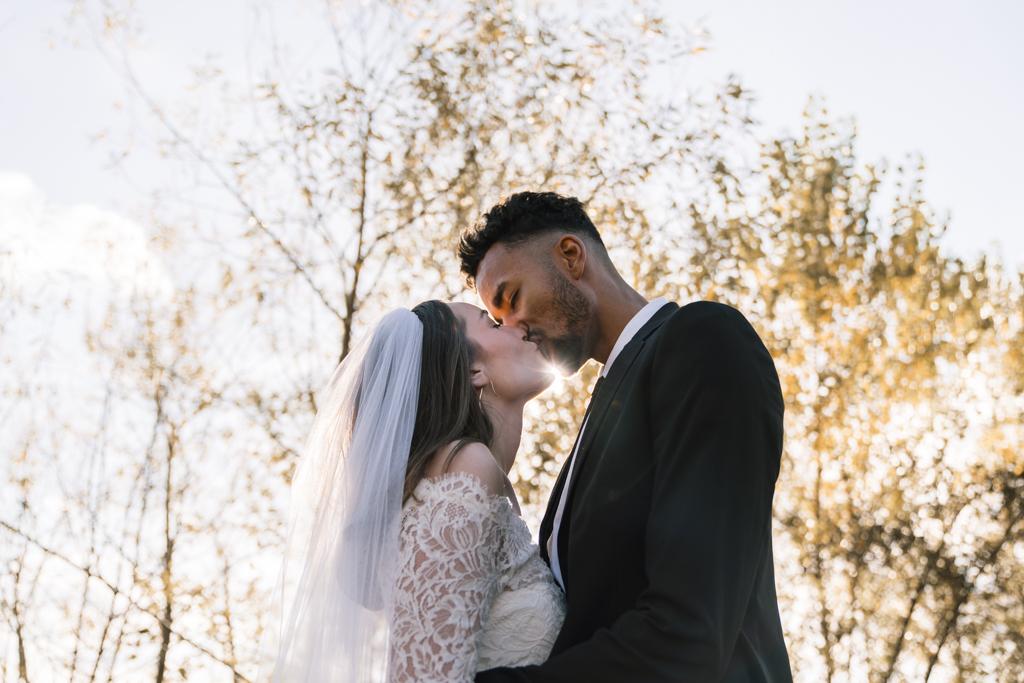 Brautpaar küsst sich im Sonnenschein.