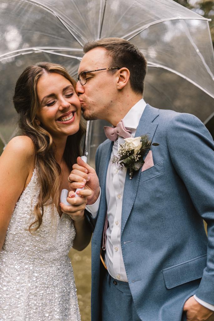 Bräutigam küsst seine Braut auf die Backe.