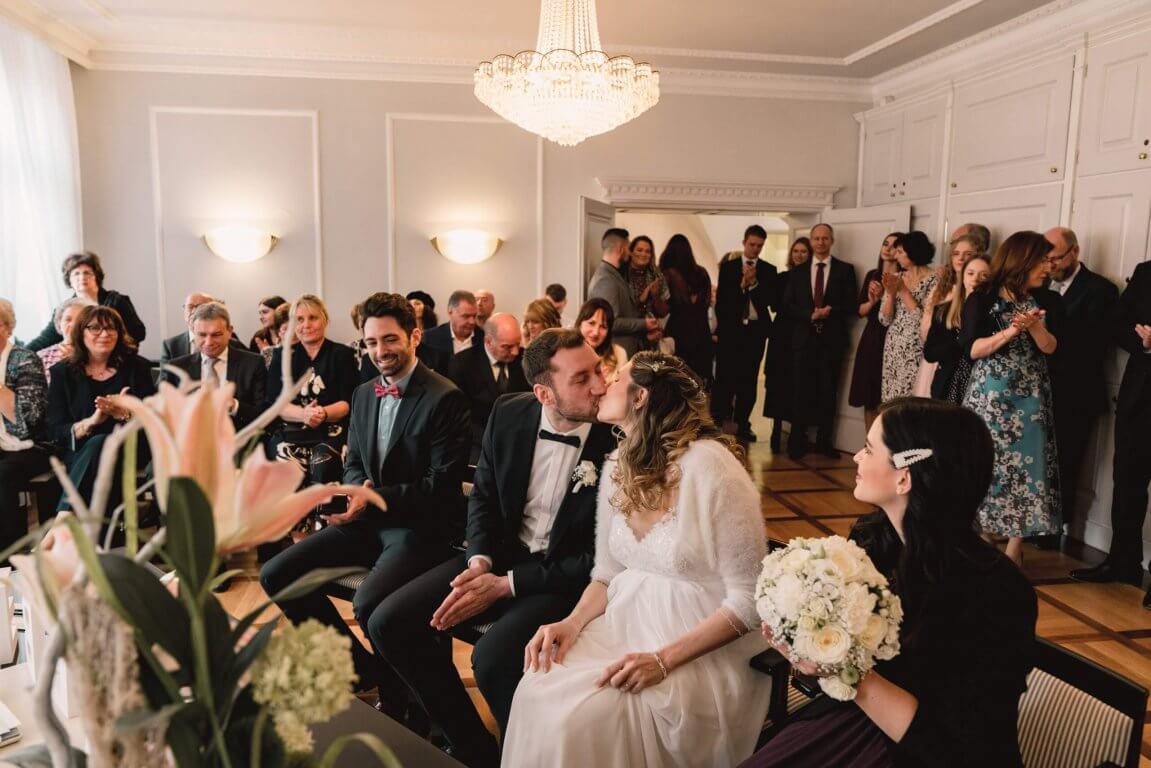 Standesamtliche Trauung Brautpaar küsst sich während die Hochzeitsgesellschaft applaudiert
