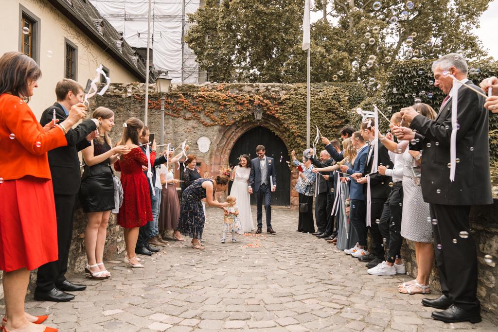 Brautpaar wird draußen von der Hochzeitsgesellschaft freudig empfangen.