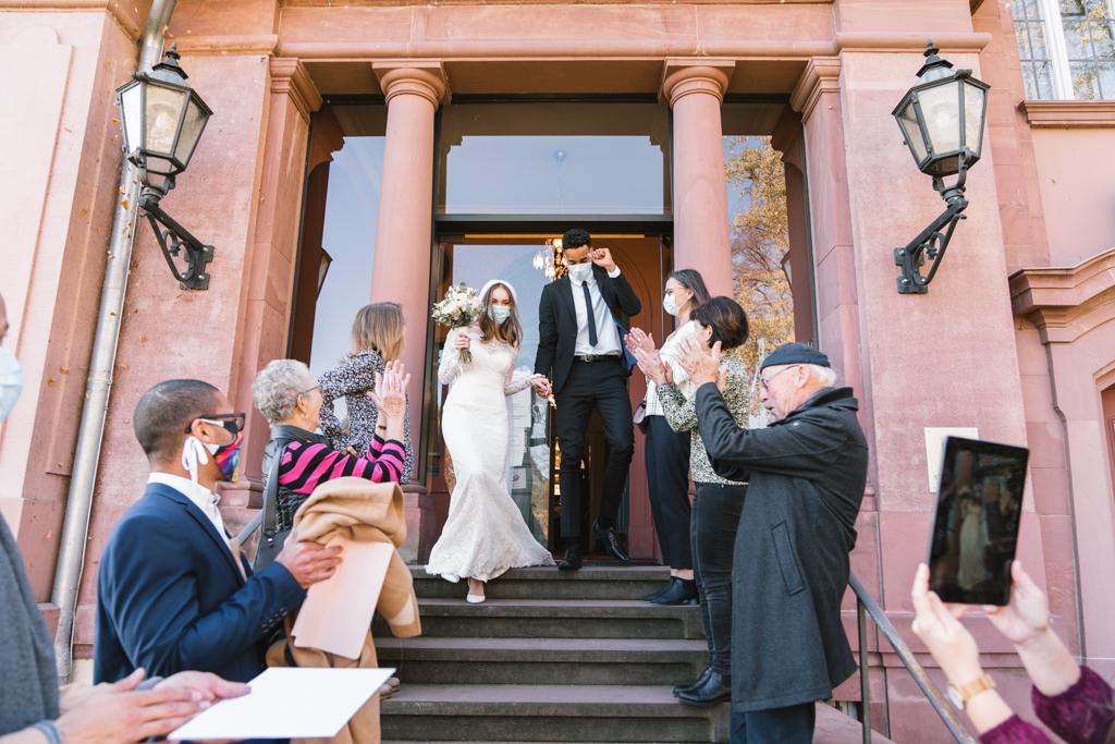 Brautpaar mit Maske verlässt das Standesamt Höchstund wird von den Gästen jubelnd empfangen.