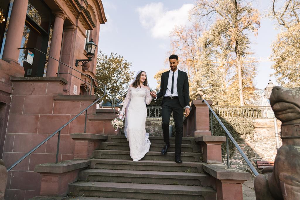 Braut und Bräutigam laufen Hand in Hand die Treppe vom Standesamt in Höchst runter.