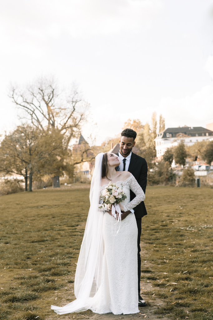 Brautpaar steht auf der Wiese und schaut sich in die Augen.