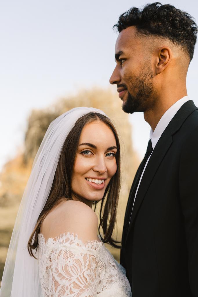 Wunderschöne Braut lacht in die Kamera im Arm ihres Bräutigams.