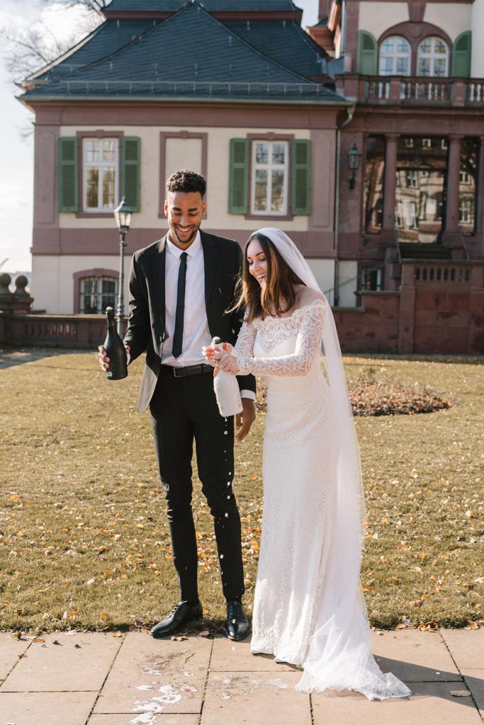 Braut und Bräutigam lassen die Sektflaschen aufspringen.