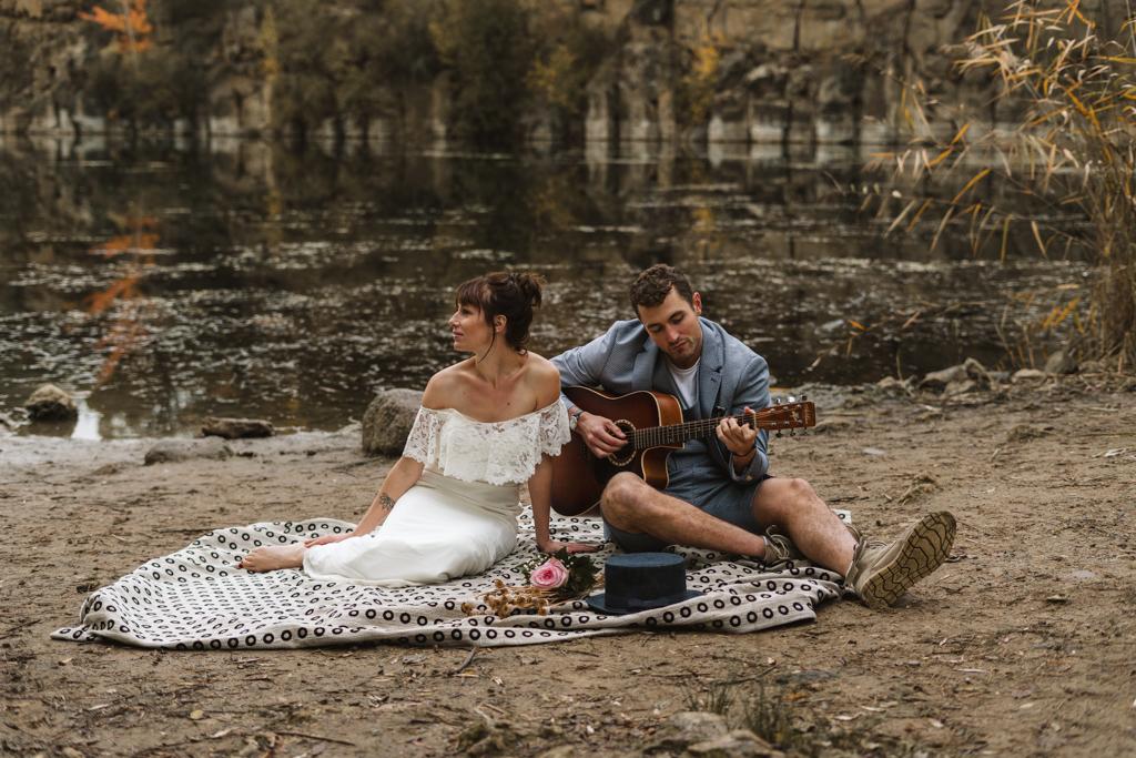 Brautpaar sitzt am See und spielt Gitarre.
